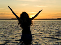 woman in the water with arms raised in happiness and prayer